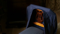 Man takes dark blue jacket from back of a chair Stock Footage