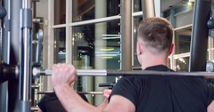 Man bodybuilder doing smith machine squat exercise with barbell at gym 4k video Stock Footage
