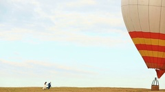 Wedding couple runs to red balloon on the field Stock Footage