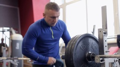 Transition shot of determined muscular man putting heavy plates on barbell and Stock Footage