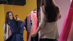 Brown-haired woman in trying blue dress in front of mirror room Stock Footage