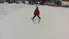 A little girl with gopro on her helmet taking her first ski lesson, HD Stock Footage