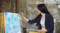 Young woman artist draw pictrure with watercolor paints and brush on easel Stock Footage