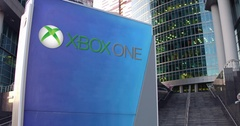 Street signage board with Xbox One logo. Modern office center skyscraper and Arkistovideo