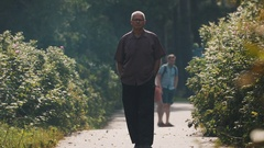 Grey-haired man in glasses walking along road in a park on a sunny day Stock Footage