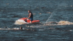 Man in vest on a jet ski fails attempt to pull surfer on wakeboard out of water Stock Footage