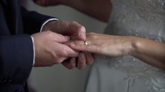 Groom in blue suit puts wedding ring on bride's tender hand Stock Footage