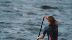 Medium shot of sportswoman in full swimsuit rides a surfboard using paddle Stock Footage