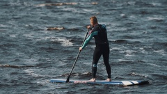 Long shot of sportsman in full swimsuit rides a surfboard using paddle Stock Footage