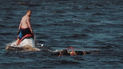 Topless man on jet ski rides around surfer, who floats in water with wakeboard Stock Footage