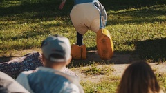 Fun race during summer festival outside. Contestants wears giant funny trousers Stock Footage