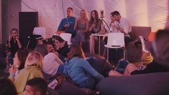 Young people smokes hookah talking, clink glasses and drink sitting on bean bags Stock Footage