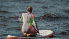 Young women in colourful swimsuit sits on a surfboard and ride it using paddle Stock Footage