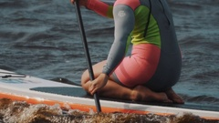 Girl in colourful swimsuit sits on a surfboard and ride it using paddle Stock Footage