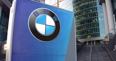 Street signage board with BMW logo. Modern office center skyscraper and stairs Stock Footage