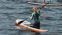 Long shot of sportswomen in full swimsuit sitting rides a surfboard using paddle Stock Footage