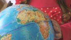 Child twists model of globe of world. Close-up Stock Footage