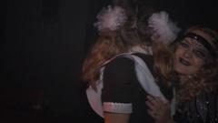 Girl in soviet school uniform dancing in crowd at halloween night club party Stock Footage