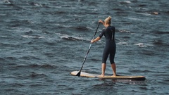 Long shot of sportswomen in full swimsuit rides a surfboard using paddle Stock Footage