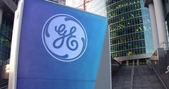 Street signage board with General Electric logo. Modern office center skyscraper Stock Footage