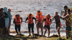 Group of young people in orange vests race each other to get paddle on a beach Stock Footage