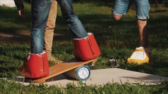 Young guy attempts to balance board on a cylinder while wearing giant boots Stock Footage