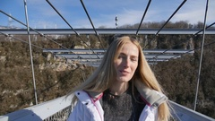 Woman walk forward thru high bridge over the canyon in front of the camera Stock Footage