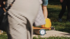 Young man attempts to balance board on a cylinder while wearing giant boots Stock Footage