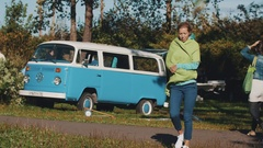 Girl walks toward camera in front of old style blue bus. Windy weather outside Stock Footage