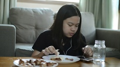 Close up shot of Asian girl eating fried chicken at home  and listening mus.. Stock Footage