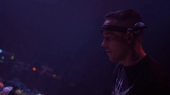 Young tattooed dj nodding his head, mixing music on turntable. Night club party Stock Footage