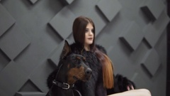 Sexy girl with long hair in black fur coat sitting near dog in studio Stock Footage