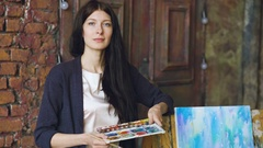 Young woman artist with watercolor paints stand near finished picture and smile Stock Footage