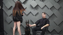 Young man and woman in stylish black clothes in the studio. Man holds doberman Stock Footage