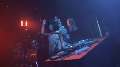 DJ girl and two dancers in halloween costumes dance on scene at night club Stock Footage