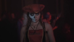 Woman in pirate hat and half painted face posing for camera at halloween party Stock Footage