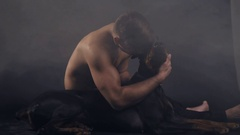 Young muscle man sits on the ground in studio with doberman in diamond necklace Stock Footage