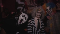Scary clown and beetlejuice posing for camera at night club halloween party Stock Footage