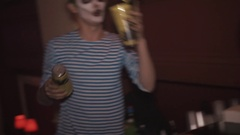 Girl dances, guy with similar face paint and juggles glasses at halloween party Stock Footage