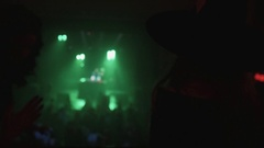 Girl in witch costume look at dancing people from balcony at halloween party Stock Footage