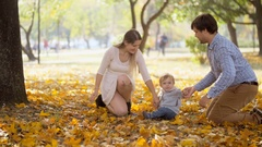 Mother and father holding baby son by hands and walking at autumn park Stock Footage