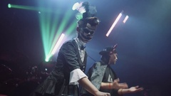 Girl and guy DJs in halloween costumes dance on scene playng music on turntable Stock Footage