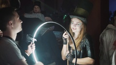 Photographer shoot girl in mad hatter costume using ringlight at halloween party Stock Footage