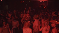 Girl in mummy zombie costume dance in crowd at night club halloween party Stock Footage