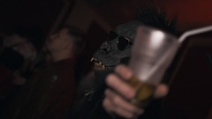 Man in vampire costume and guy in monkey mask have drinks at halloween party Stock Footage