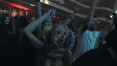 Girl in scary toy animal half mask dance in crowd at night club halloween party Stock Footage