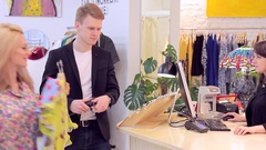 Beautiful caucasian couple choose clothes in the store and goes to cash-desk Stock Footage