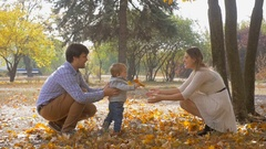 Slow motion footage of parents encouraging baby son to make first steps Stock Footage