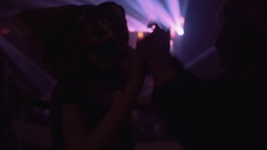 Girl in giant cat head mask dance holding hand with friend at night club party Stock Footage
