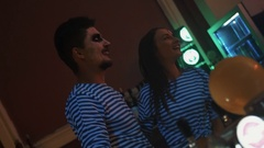 Guy an girl bartenders in stripe shirts and face paint have drinks and laughing Stock Footage